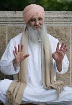 Guru Dev sitzend,lachend und Handflächen zum Betrachter