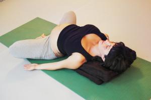 Schwangere macht Yoga.Hier in Rückenlage, unterstützt, Beine angewinkelt.