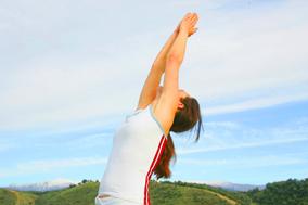 Yogalehrerin macht Yoga Rückbeuge vor blauem Himmel und grünen Bergen