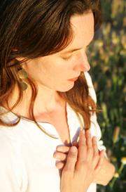Yogalehrerin Birgit Braune im Halbprofil in Meditation. Beide Hände vor dem Herzen verschränkt.